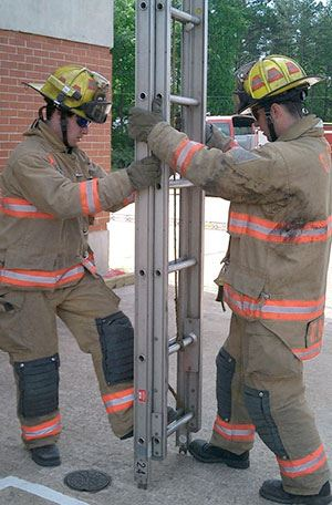 Two firefighters work on ladder technique during a training exercise