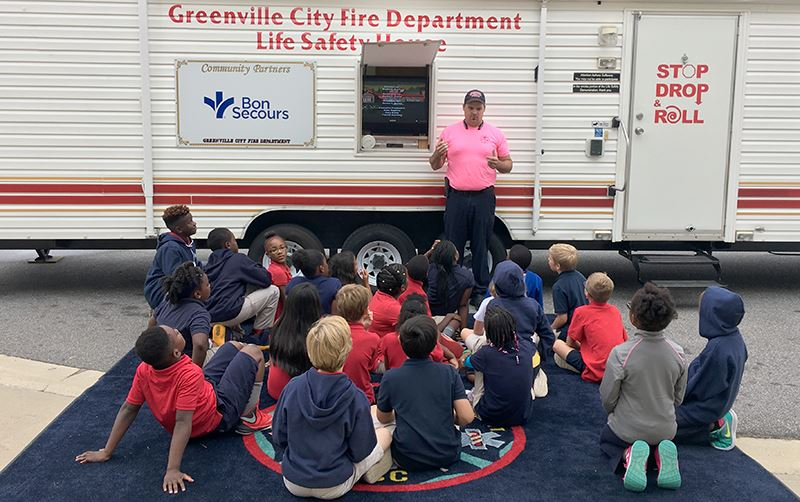 Firefighter talking to students at the Fire and Life Safety House