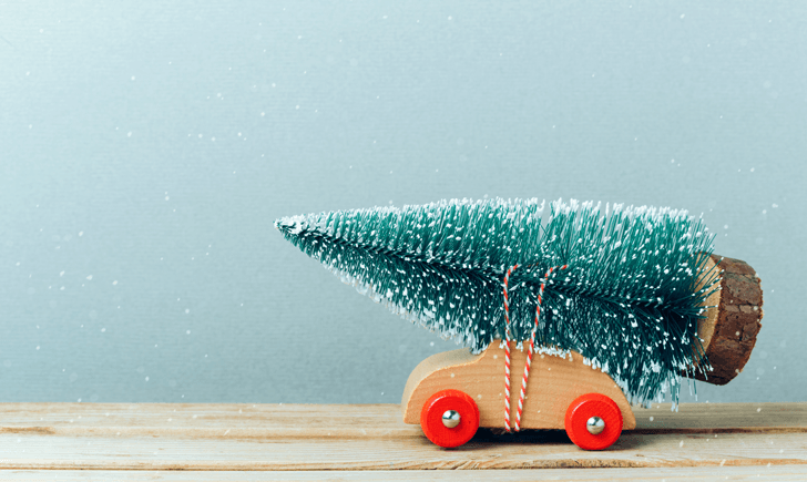 A toy car with a toy Christmas tree strapped on the top